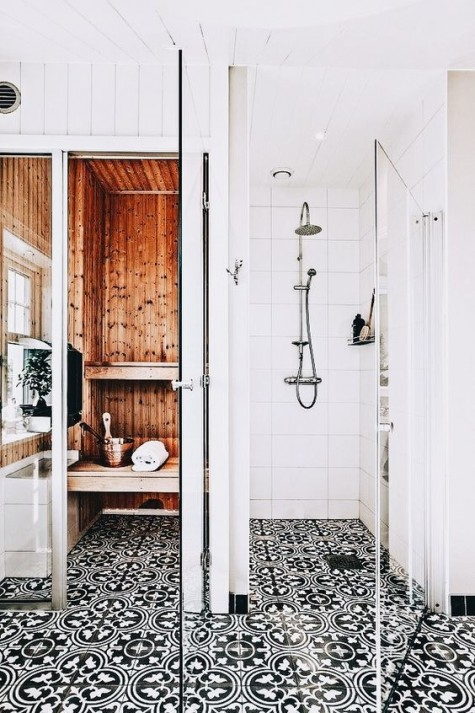 a contemporary bathroom with black and white patterned mosaic tiles on the floor and white tiles on the walls