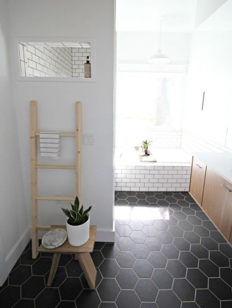 black hex tiles on the floor and white subway tiles on the walls make up a bold and stylish pair