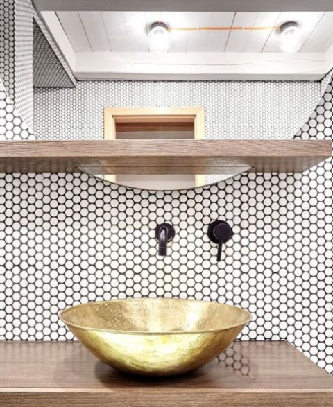 white penny tiles with black grout and fixtures and a brass bowl sink look very chic
