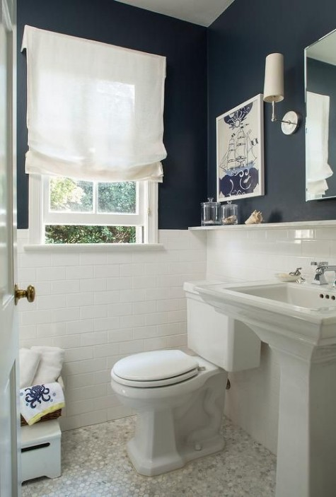 white subway tiles with white grout and navy walls create a cool contrast in the small bathroom
