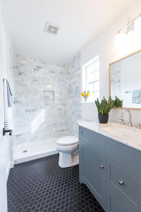 a neutral bathroom with marble tiles, navy hexagon tiles on the floor and a powder blue vanity