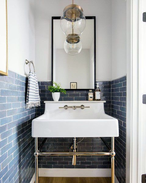 a small sink space clad with blue subway tiles and white grout plus a vintage sink and a pendant lamp