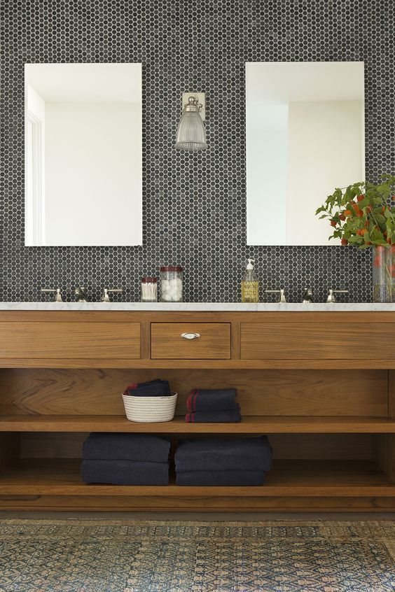 black penny tiles with white grout, a stained wooden vanity and a marble countertop for a chic and elegant look