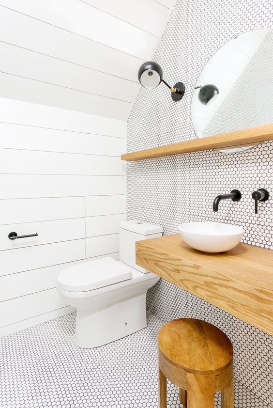 a contemporary bathroom with white penny tiles with black grout, black lamps and fixtures plus a wooden vanity