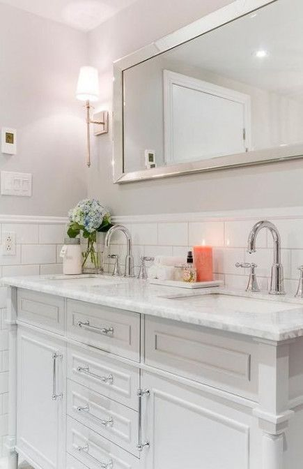a neutral and elegant sink space with white subway tiles, a marble countertop and silver touches here and there