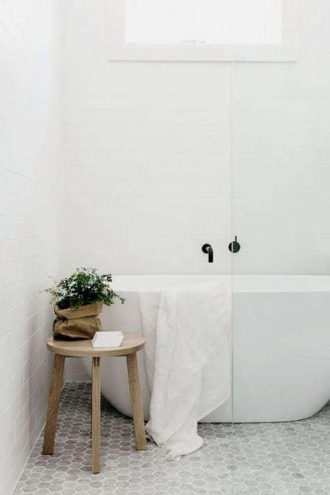 a contemporary bathroom with white subway tiles on the walls and marble hex tiles on the floor