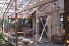 17 a large cat enclosure with floor cushions, a comfy round chair and a large bench for cats and people to stay in