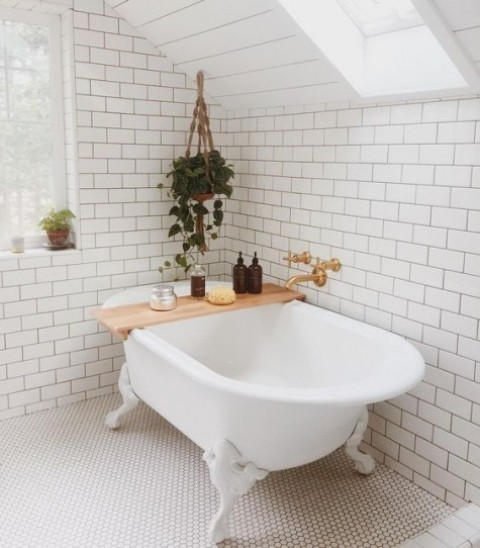 a modern airy bathroom with white subway and penny tiles on the floor plus greenery to refresh the space