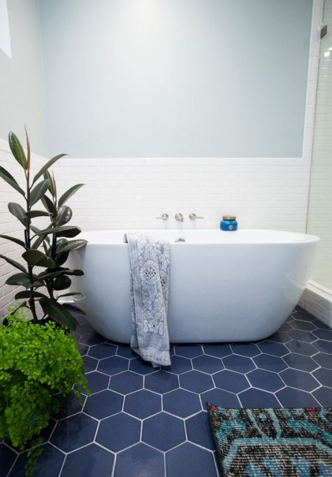 navy hex tiles with white grout and white tiles on the walls make the bathroom bold, contrasting and catchy