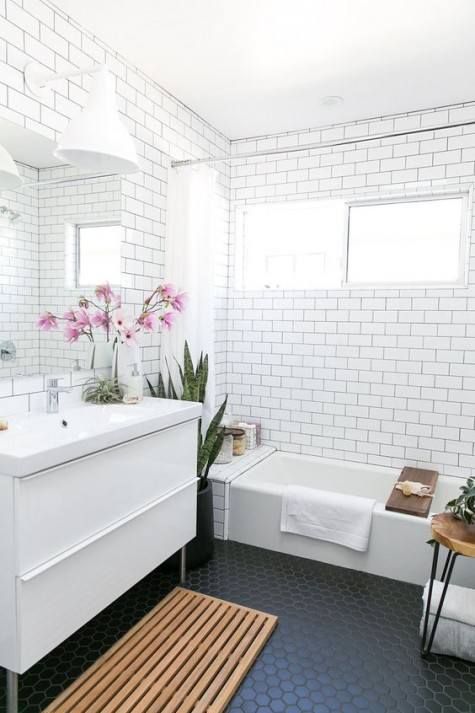 a monochrome modern bathroom with white subway tiles and black hex ones on the floor