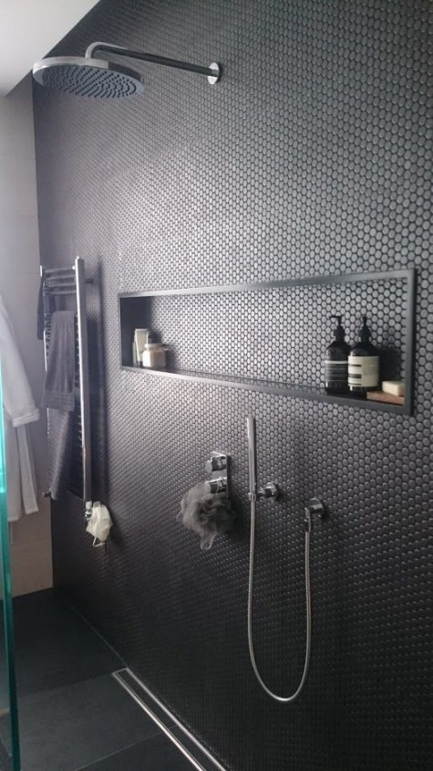 matte black penny tiles make the dark masculine shower more eye-catchy and more contemporary and fresh