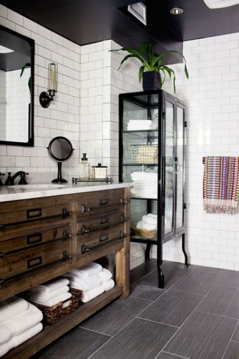 a vintage inspired bathroom with white subway tiles and black grout plus black accessories