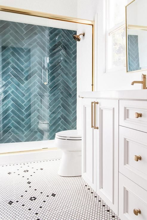 a white penny tile floor with a pattern and a blue herringbone pattern tile wall in the shower