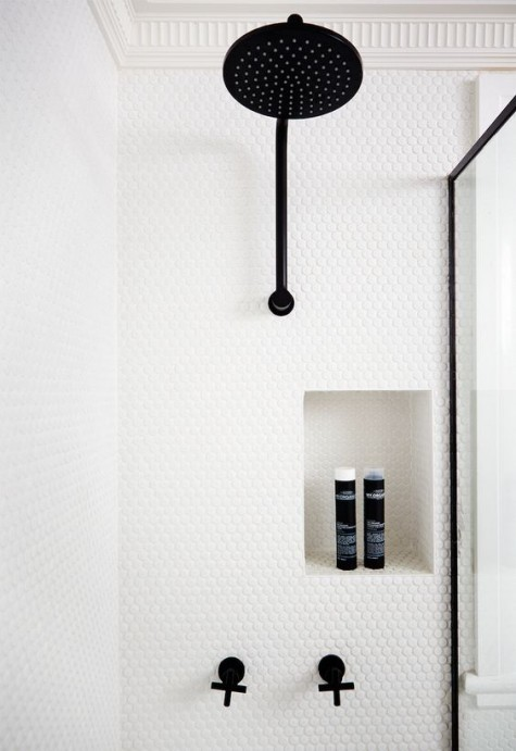 white penny tiles in the shower with black fixtures make the space contemporary, bold and very eye-catchy