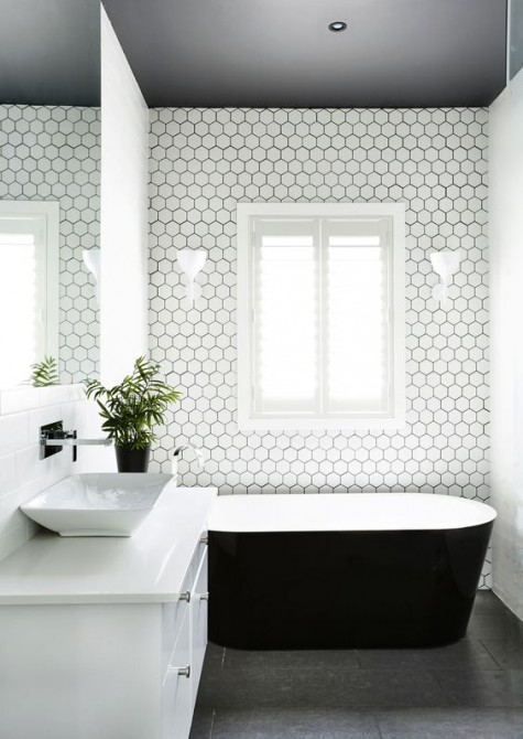 a monochromatic bathroom with small white hex tiles with black grout accentuate the bathtub space