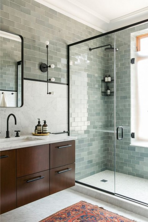 aqua and seafoam subway tiles paired with a dark stained vanity and black touches for a bold feel
