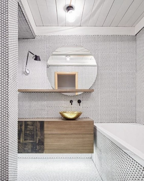 white penny tiles with black grout used all over the bathroom make the space look very eye-catchy