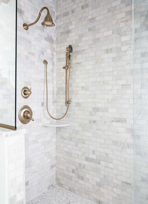 a shower space done with marble tiles and marble penny tiles plus copper fixtures for a vintage touch