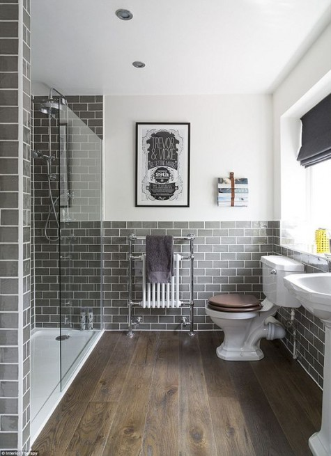 grey bathroom tiles with white grout and wood floors look chic together