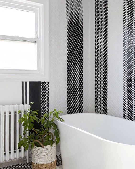 a bathtub backsplash made of black and white penny tiles clad in stripes and fresh greenery to enliven the space