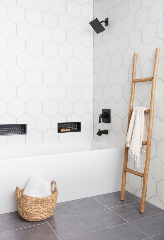 a contemporary bathroom with white hex tiles on the walls and grey tiles on the floor