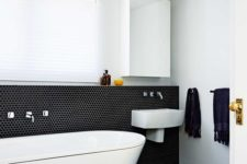 25 bathroom clad with black penny tiles and white grout, with white appliances and a yellow stool