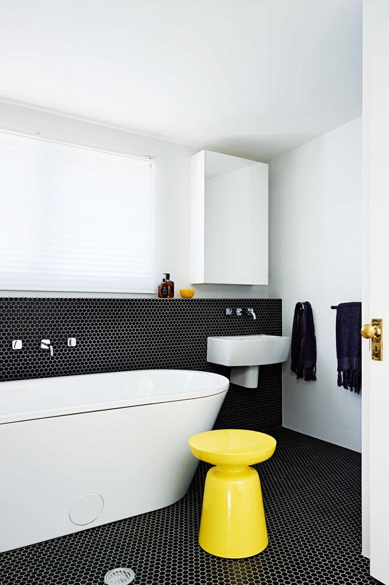 bathroom clad with black penny tiles and white grout, with white appliances and a yellow stool