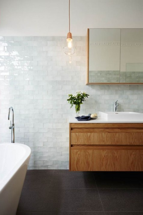 soft aqua color subway tiles create a very relaxing bathroom, and warm woods add coziness to it