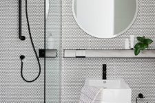 26 a minimalist space done with black tiles on the floor and white penny tiles on the walls