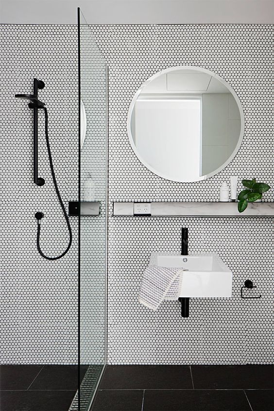 a minimalist space done with black tiles on the floor and white penny tiles on the walls