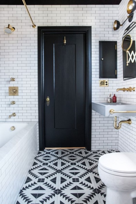 white subway tiles and mosaic monochromatic tiles on the floor and a black door for a monochromatic space