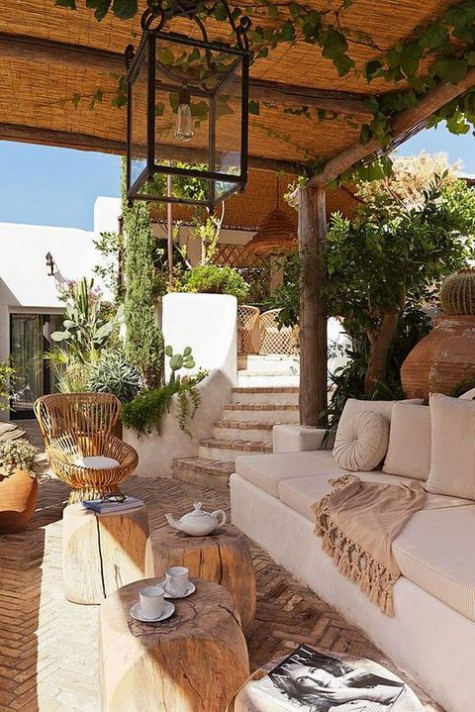 Mediterranean terrace with tree stump stools, rattan chairs, greenery and cacti plus pendant lamps
