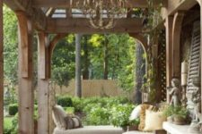 a French country chic neutral terrace with a refined chandelier, wooden furniture with upholstery and lots of greenery