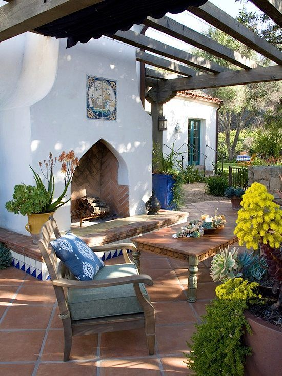 a Mediterranean patio done with a large fireplace decorated with azulejo tiles, vintage wooden furniture and bright blooms