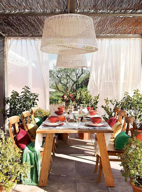 a Mediterranean rustic terrace with a dining space with a wooden dining set, colorful throws and blankets, terracotta and wicker lamps