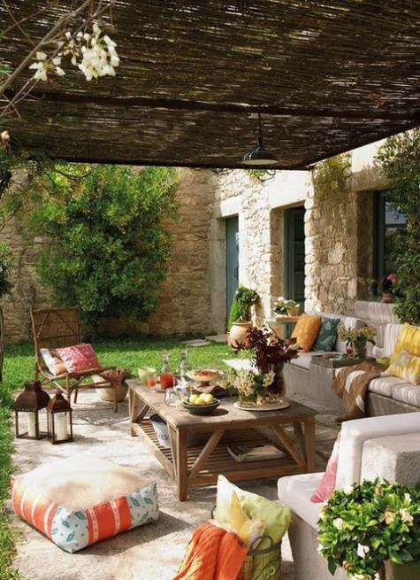 a Mediterranean terrace with bright throws, ottomans, floor cushions, wooden furniture and potted blooms and greenery