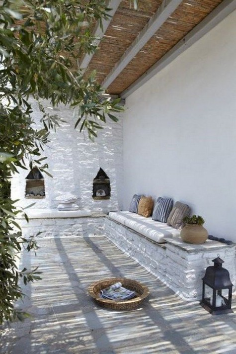 a Mediterranean terrace with white stone and plaster wlals, niches for storage, printed throws and candle lanterns