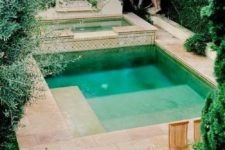 a Moroccan backyard with a plunge pool, a hot tub, wooden furniture and warm-colored tiles