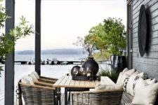 a Nordic space with wicker chairs, a wooden table and bench, lots of greenery in pots and blakc tableware