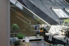 a Nordic terrace with a printed rug, a black sofa with pritned pillows, potted greenery and a small table