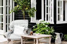 a Nordic terrace with natural wooden furniture, potted greenery and a tree, rattan chairs
