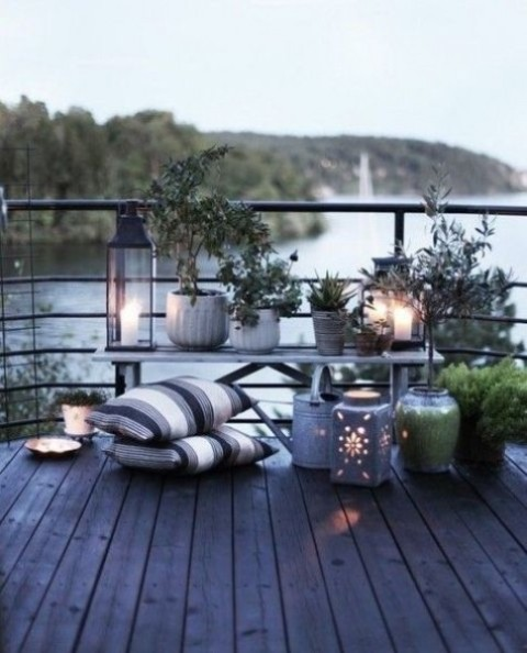 a Nordic terrace with pots and planters with greenery, succulents, candle lanterns and striped pillows