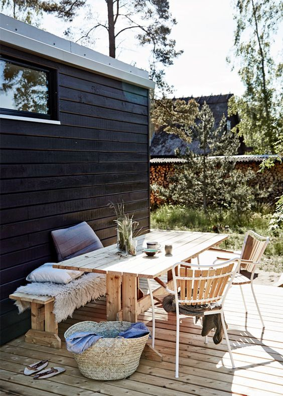 a Scandinavian terrace with a dining zone with wooden furniture and forged chairs, a basket and some greenery
