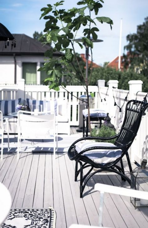 a Scandinavian terrace with a potted greenery and a tree, with white and black furniture and a simple rug