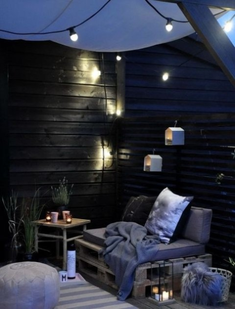 a Scandinavian terrace with birdhouse lights, potted greenery, lots of candles and crate and wooden furniture