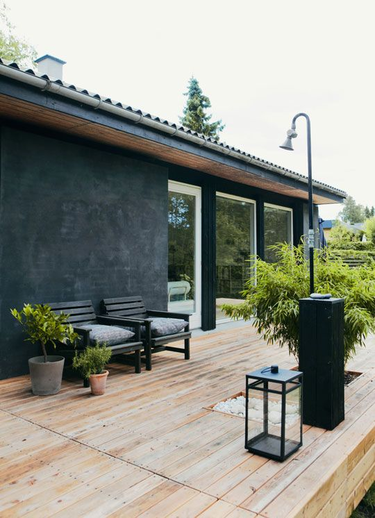 a Scandinavian terrace with black chairs, candles lanterns, a large planter and smaller ones with greenery