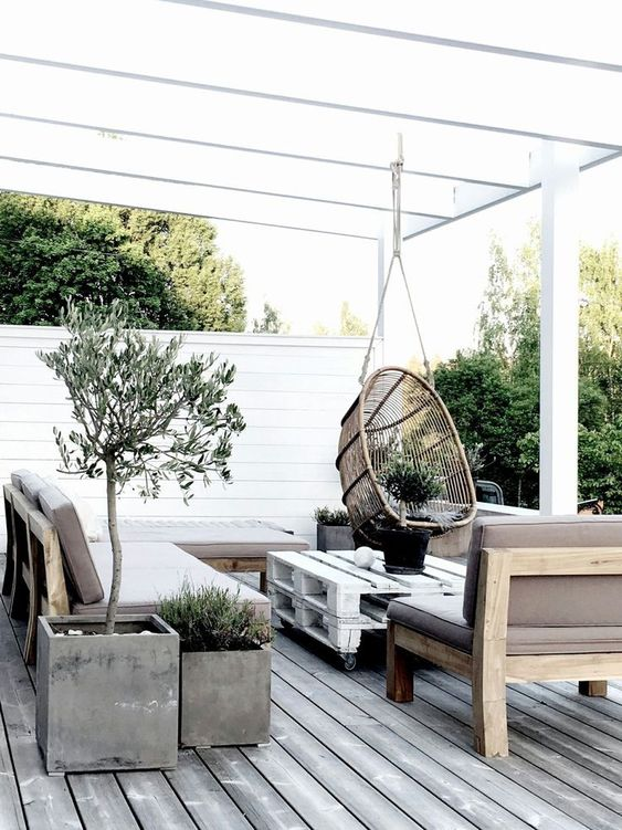 a Scandinavian terrace with concrete planters, wooden and pallet furniture and a hanging rattan chair