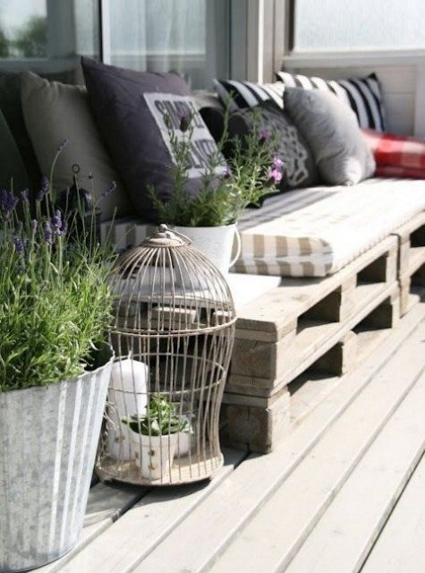 a Scandinavian terrace with crate furniture, printed pillows, potted greenery and blooms, a cage with candles and greenery