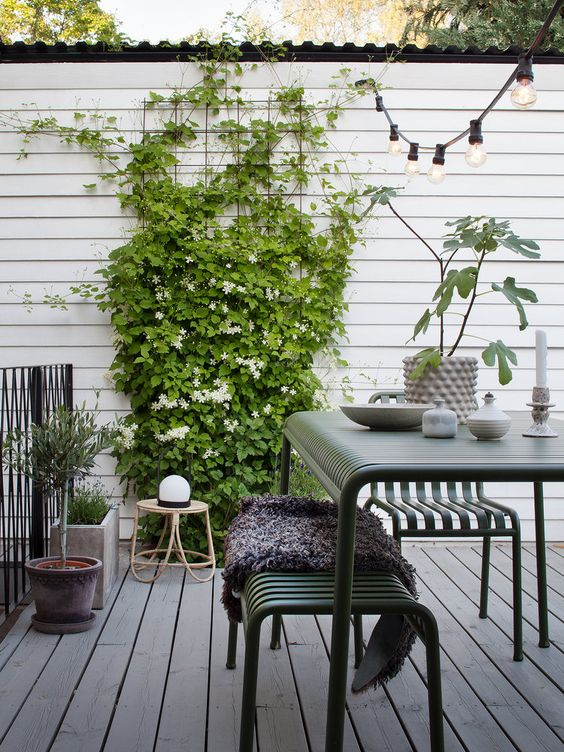 a Scandinavian terrace with dark green metal furniture, climbing greenery and blooms, potted plants and a rattan chair
