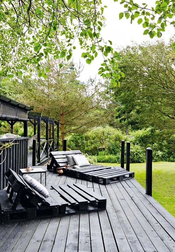 a black Scandinavian terrace with pallet loungers, a small table and printed textiles plus lots of greenery around